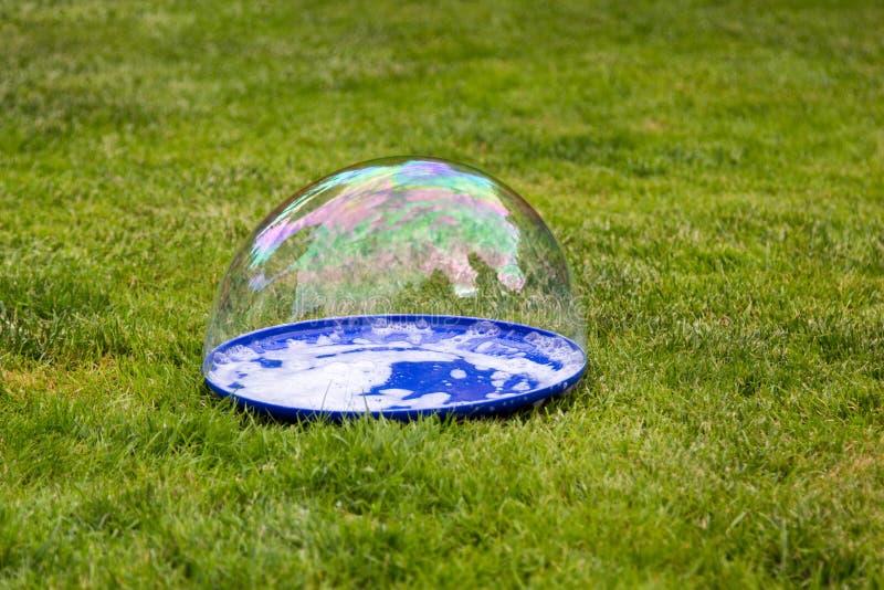 La grande bolla si trova su un piatto su erba fotografia stock