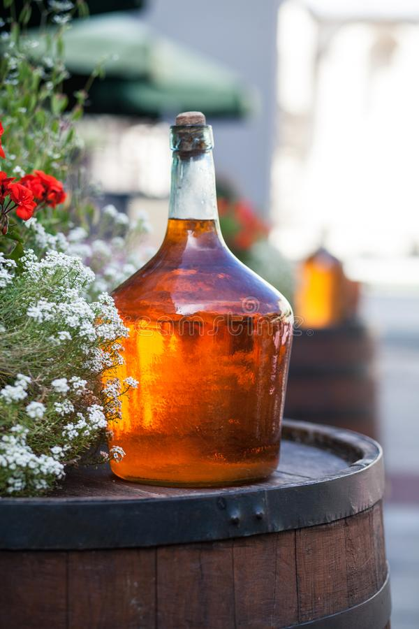 La grande bouteille de vin fait maison sont sur le baril image stock