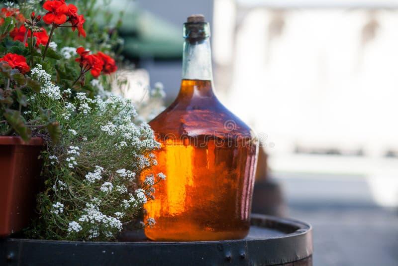La grande bouteille de vin fait maison sont sur le baril images stock