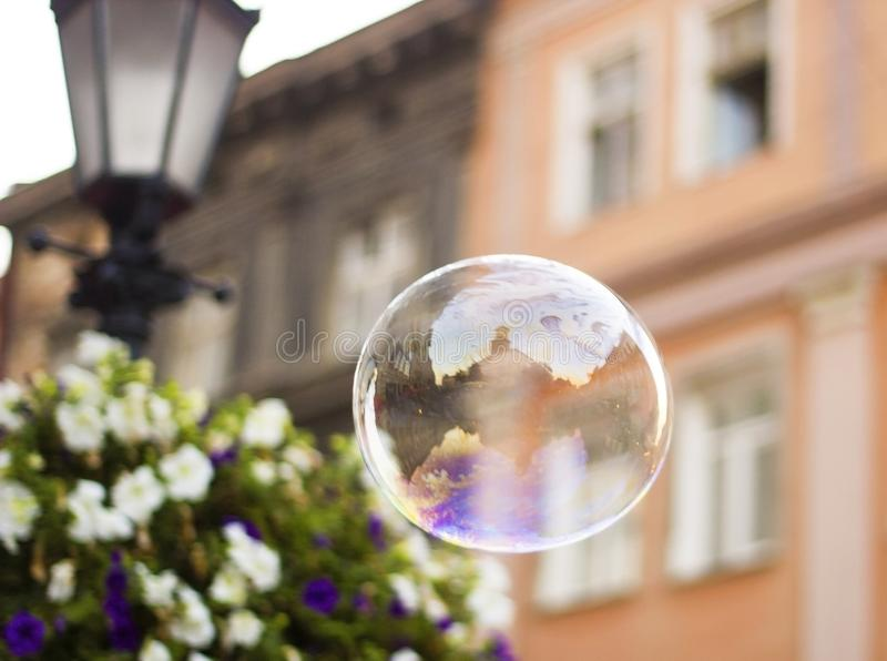 La grande bulle de savon vole par l'air dans la ville photographie stock libre de droits