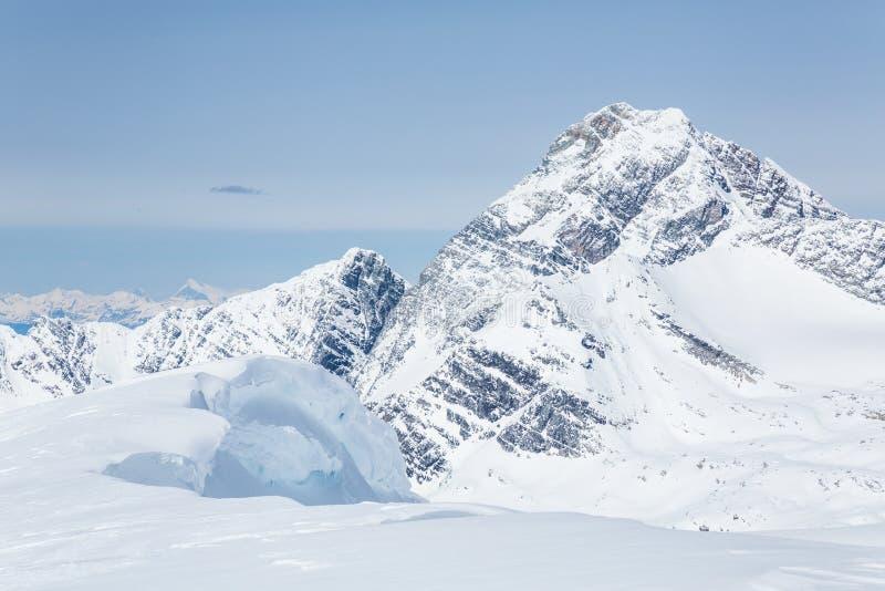 La grande corniche de la neige surplombante des jeunes font une pointe regarder le bâti Sir Donald photos stock