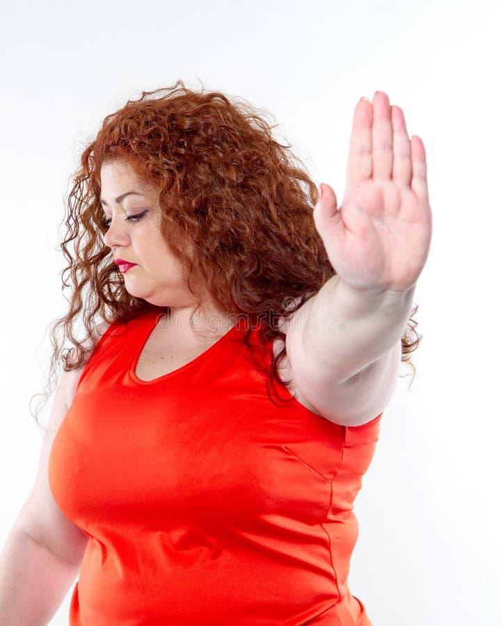 La grande donna con rossetto rosso e grande dolore addominale, cattivo umore fotografia stock libera da diritti