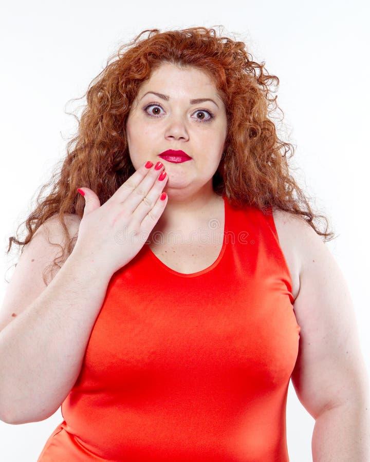 La grande donna con rossetto rosso e grande dolore addominale, cattivo umore immagine stock