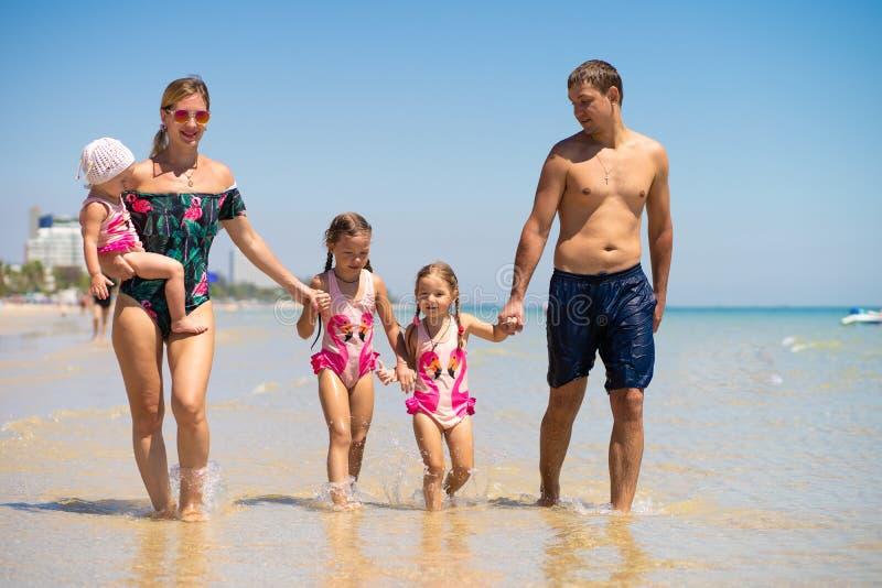 La grande famiglia felice sta divertendosi alla spiaggia concetto di una famiglia numerosa in mare Modo della spiaggia immagine stock libera da diritti