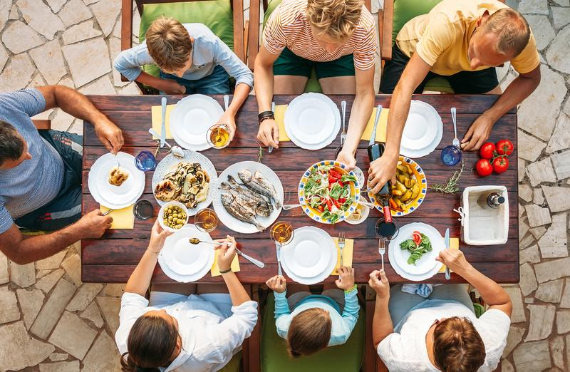 La grande famiglia ha una cena con il piatto cucinato fresco sul giardino aperto t fotografie stock libere da diritti