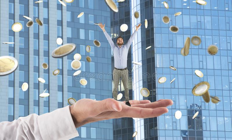 La grande main tient un homme d'affaires qui réalise le succès photos stock