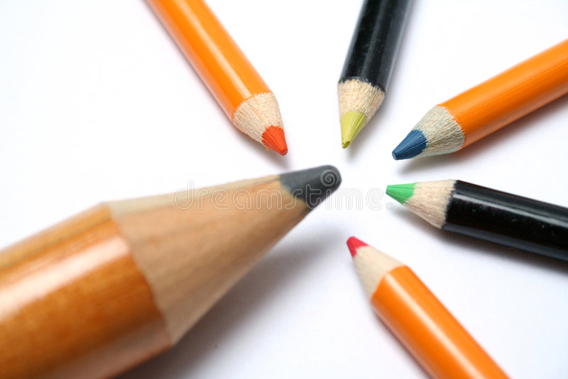 La grande matita e cinque piccole matite di colore su una diagonale fotografia stock libera da diritti