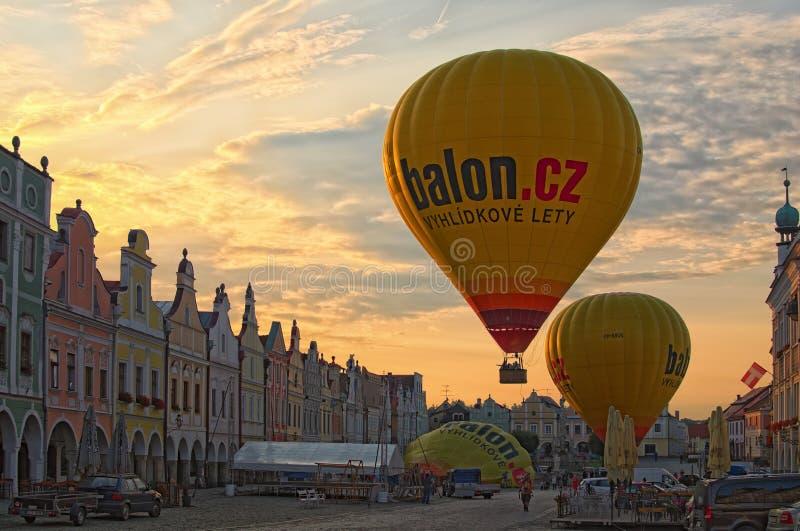 La grande mongolfiera gialla decolla dal quadrato principale della città Telc Altre due mongolfiere stanno preparando decollare immagini stock libere da diritti