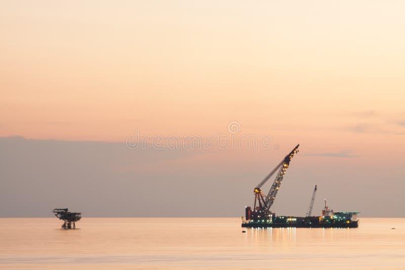 La grande nave della gru che installa la piattaforma dentro al largo, chiatta gru che fa l'installazione pesante marina dell'ascen fotografie stock
