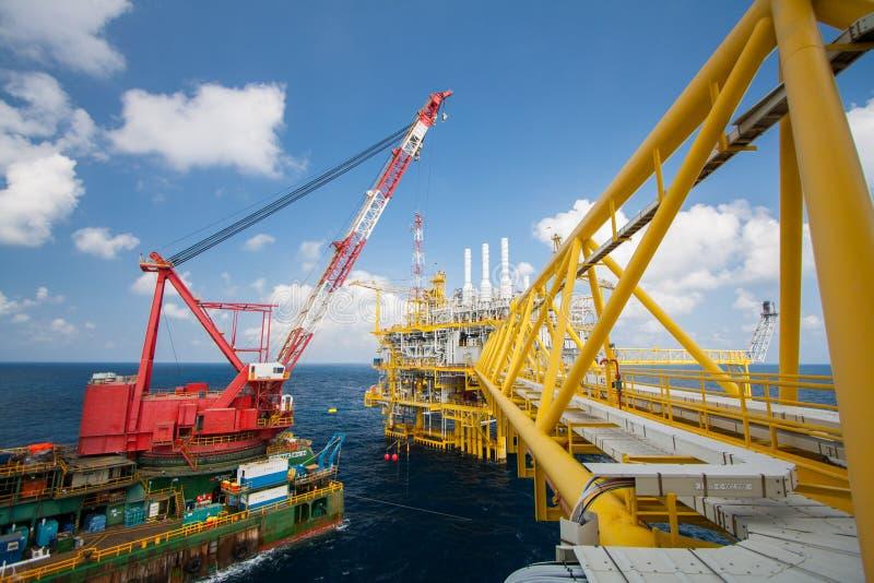 La grande nave della gru che installa la piattaforma dentro al largo, chiatta gru che fa l'installazione pesante marina dell'ascen fotografia stock