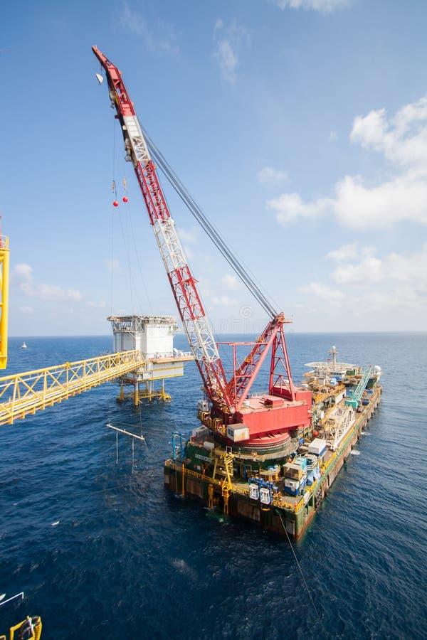 La grande nave della gru che installa la piattaforma dentro al largo, chiatta gru che fa l'installazione pesante marina dell'ascen fotografia stock libera da diritti