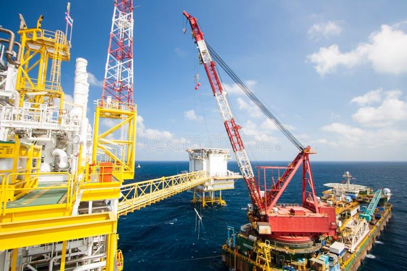 La grande nave della gru che installa la piattaforma dentro al largo, chiatta gru che fa l'installazione pesante marina dell'ascen immagine stock
