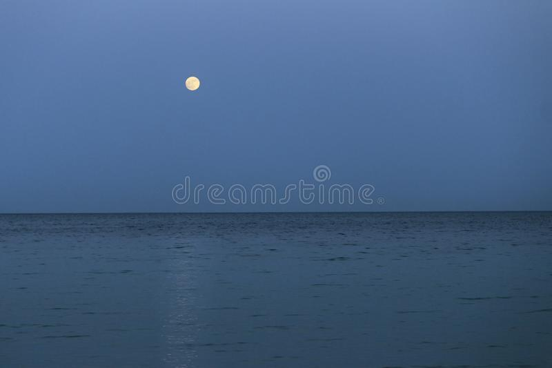 La grande pleine lune se lève au-dessus de la mer au crépuscule images stock