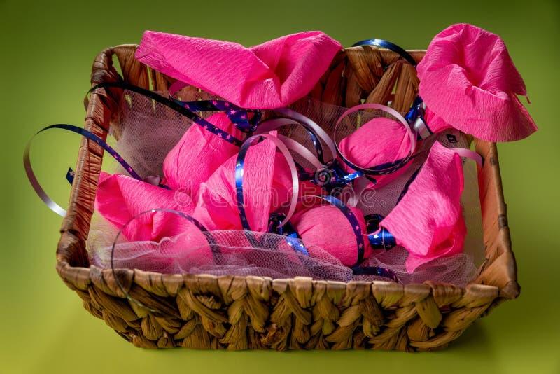 La grande sucrerie cinq enveloppée en papier rose d'enveloppe avec le ruban bleu sont dans le panier en osier brun sur le fond/ta photo stock