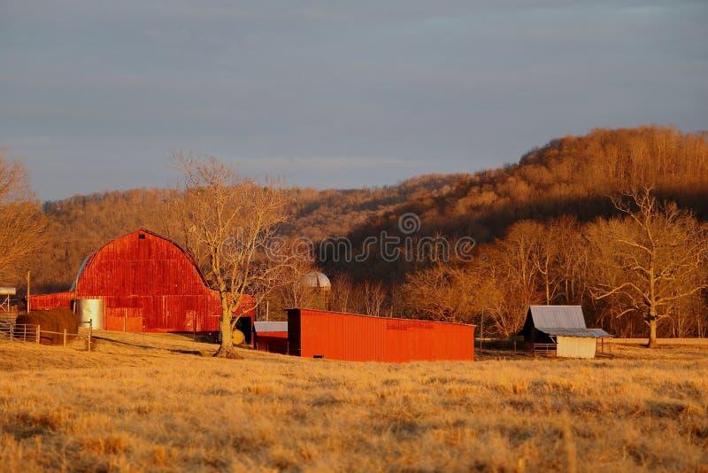 La grange rouge se tient dans les cieux orageux ci-dessus photo libre de droits