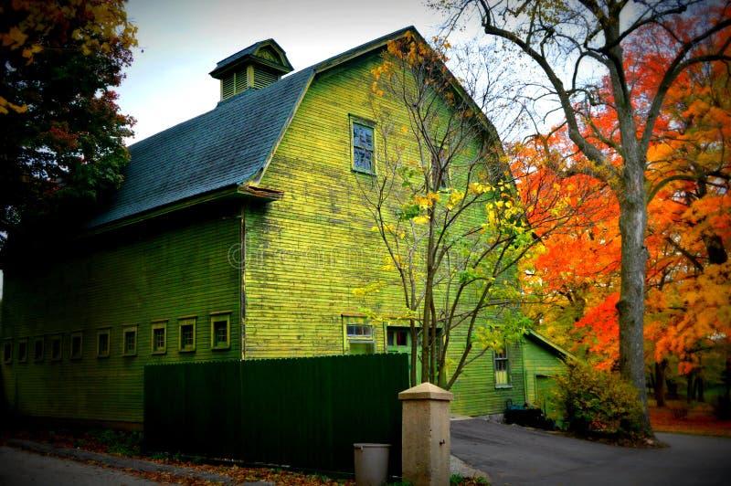 La grange verte avec l'automne colore l'avant photos stock