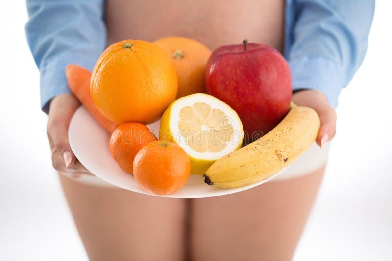 La gravidanza e la nutrizione sono a dieta - la donna incinta con il isolat di frutti fotografie stock libere da diritti