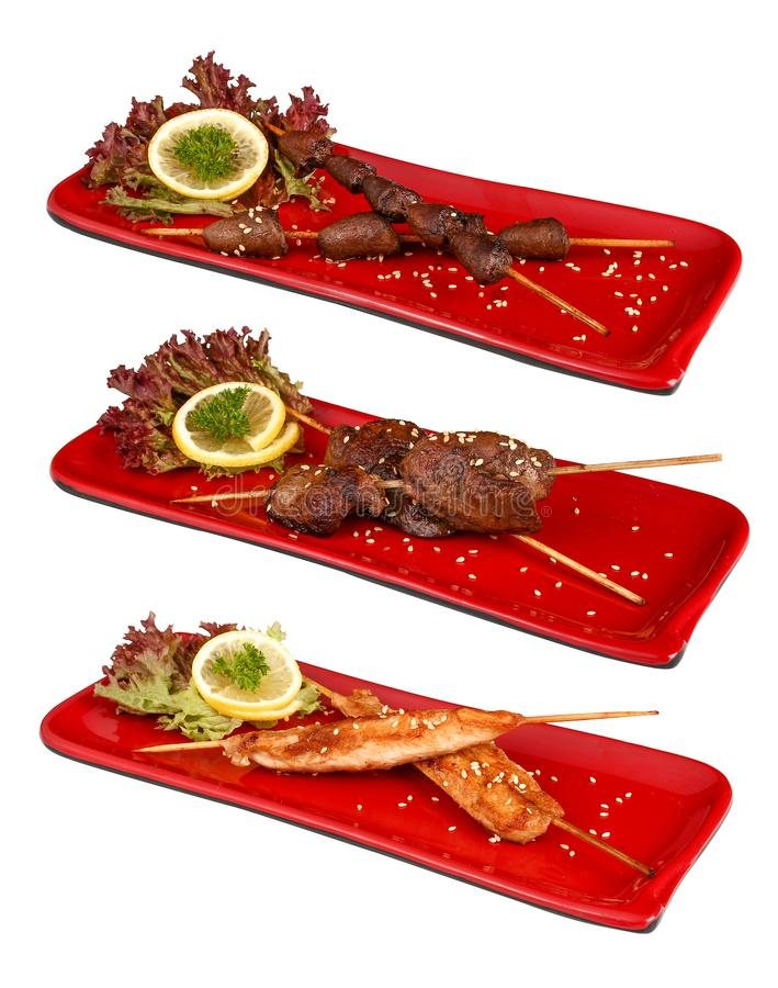 La griglia giapponese Yakitori ha messo in un piatto rosso Piatto tradizionale giapponese Su una priorit? bassa bianca fotografia stock