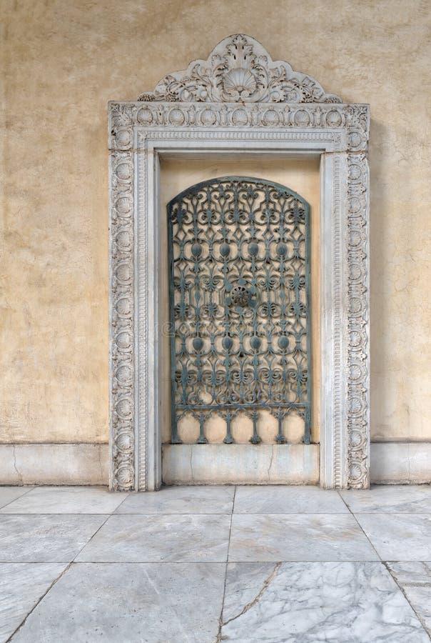 La griglia verde decorata antica del ferro incorniciata dalla struttura di marmo decorata sopra la parete di pietra beige ed il m fotografia stock libera da diritti