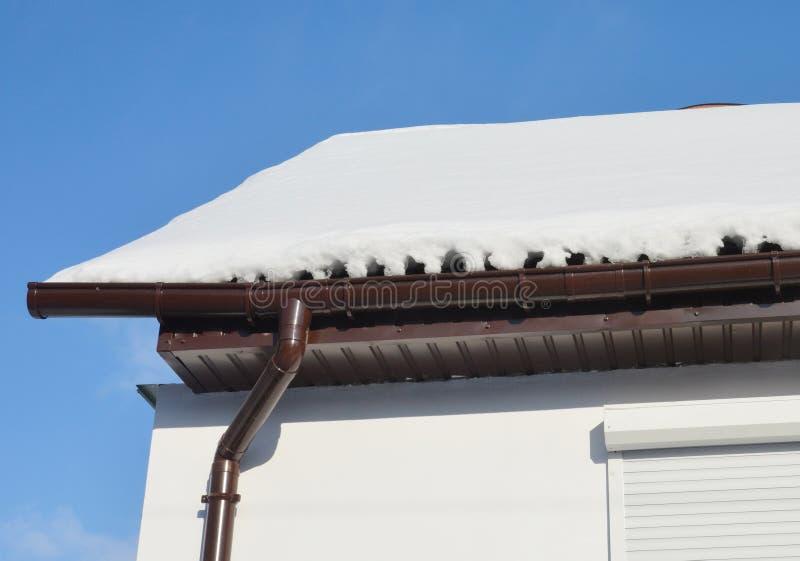 La grondaia della pioggia e del tetto ha coperto la neve ed il ghiaccio nell'inverno immagini stock
