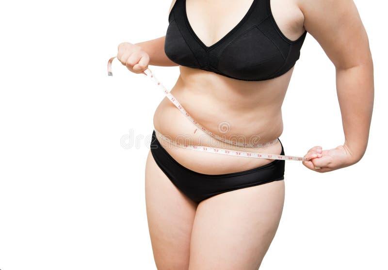 la grosse compression d'exposition de femme serrent la graisse du corps par concept de poids excessif de bande de mesure photos stock