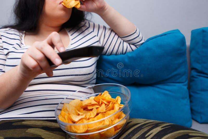 La grosse femme de poids excessif s'asseyant sur le sofa, mangeant ébrèche tandis que wat photos stock