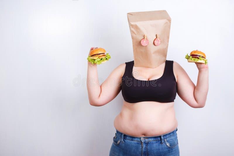 La grosse femme obèse avec un sac de papier sur la tête aiment un masque avec des yeux photos libres de droits