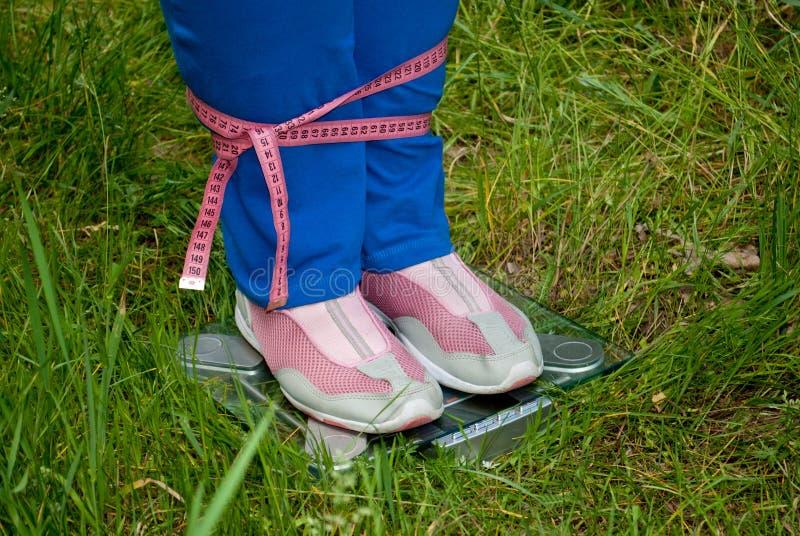 La grosse femme perdent le poids se tenant à gauche en longueur sur les échelles que les jambes ont relié la bande de mesure rose photo libre de droits