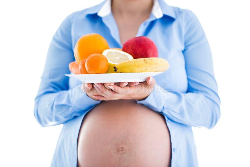 La grossesse et la nutrition suivent un régime - la femme enceinte avec l'isolat de fruits photos libres de droits