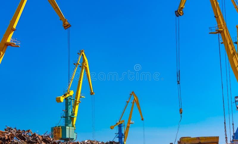 La gru della ferraglia con molto metallo in porto marittimo immagini stock