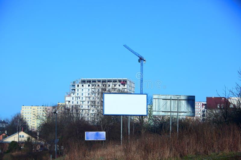 La gru di costruzione è visibile contro lo sfondo del panorama della città con un cielo blu senza nuvole immagini stock
