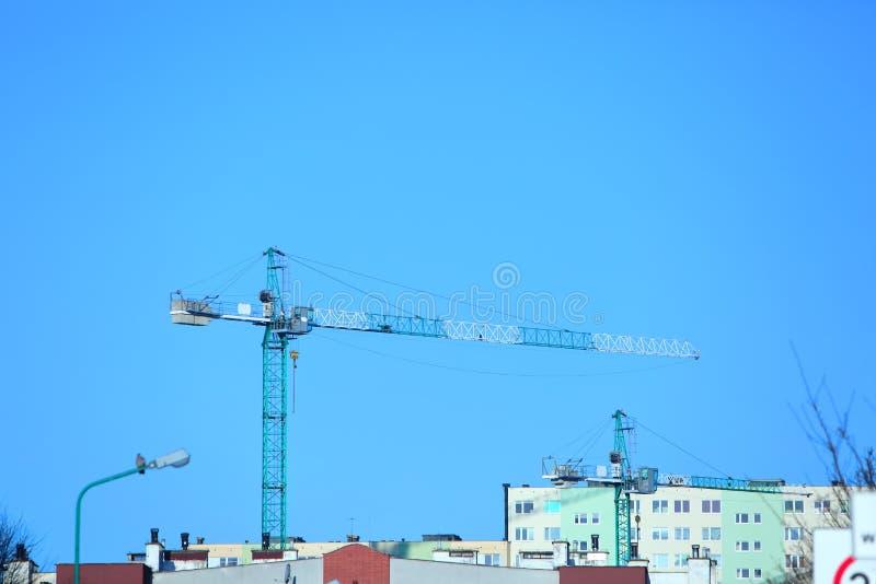 La gru di costruzione è visibile contro lo sfondo del panorama della città con un cielo blu senza nuvole fotografie stock