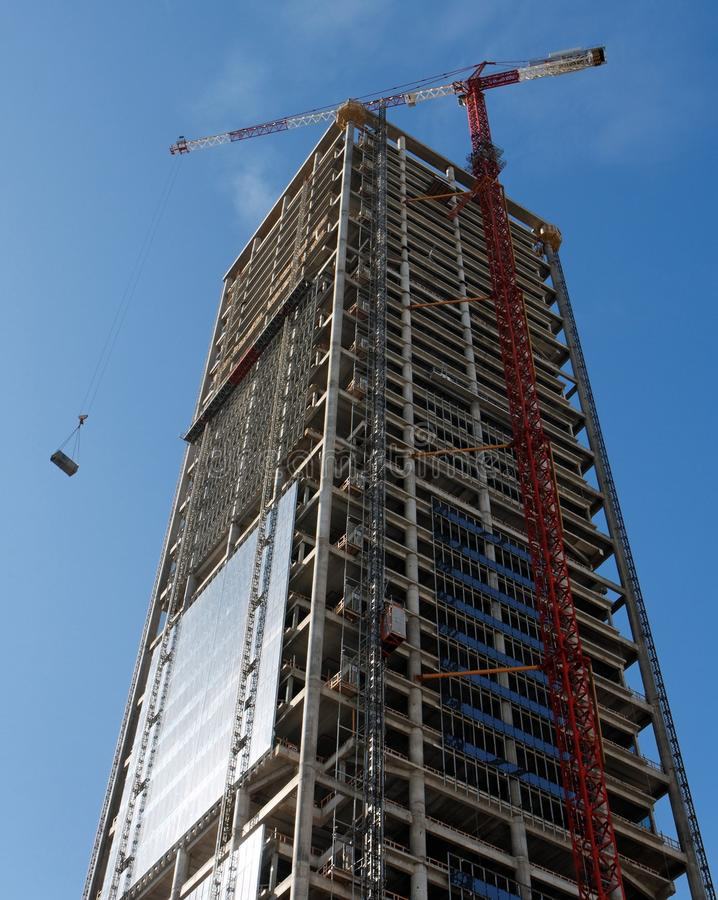 La gru di sollevamento che solleva un peso al grattacielo cons fotografie stock libere da diritti