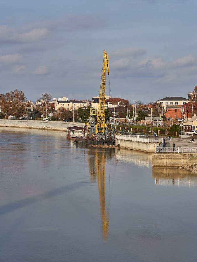 La gru gialla sulla chiatta è riflessa nell'acqua del fiume di Kuban contro lo sfondo del paesaggio urbano immagini stock libere da diritti