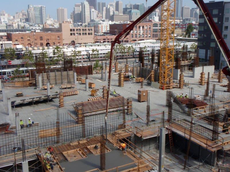 La gru versa il cemento come impianti della gente al cantiere immagini stock libere da diritti