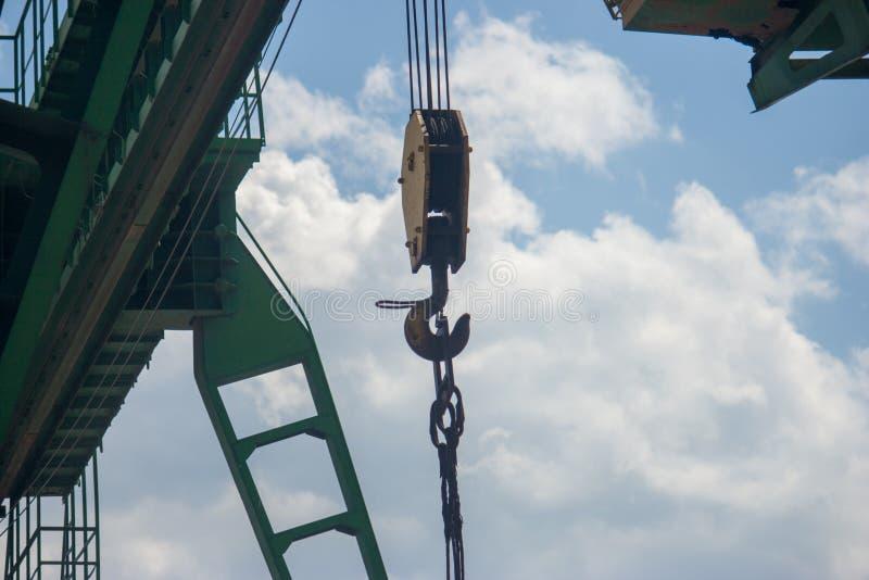 La grue de pont est tirée de dessous contre le ciel bleu et les nuages blancs photographie stock libre de droits