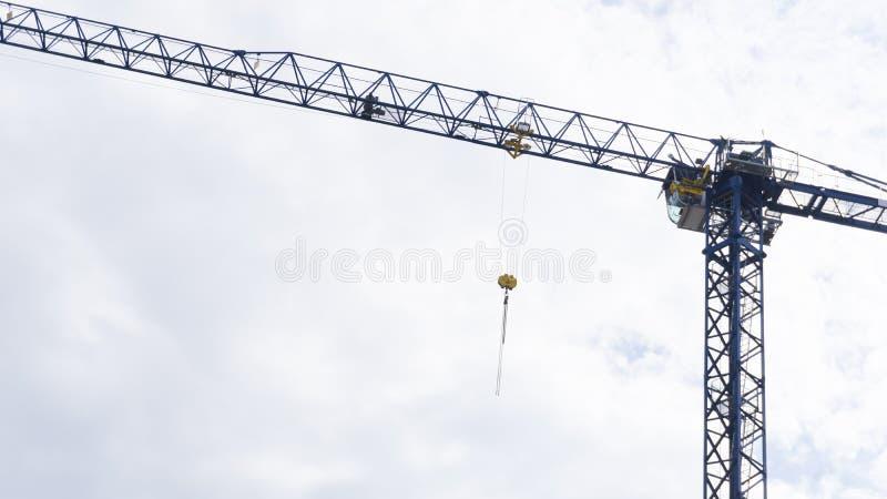 La grue/grues sur le ciel bleu avec des nuages pour la publicité de construction conçoivent image libre de droits