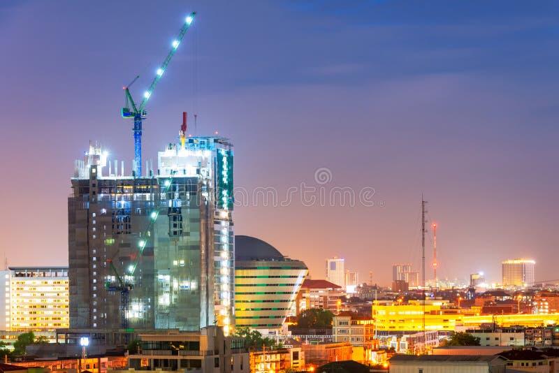 La grue industrielle résistante occupée fonctionnent au chantier de construction photographie stock libre de droits