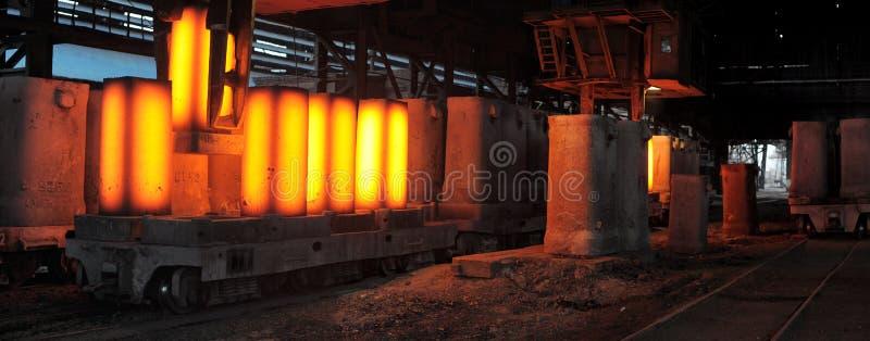 La grue retire des formes des porcs en acier heated images stock