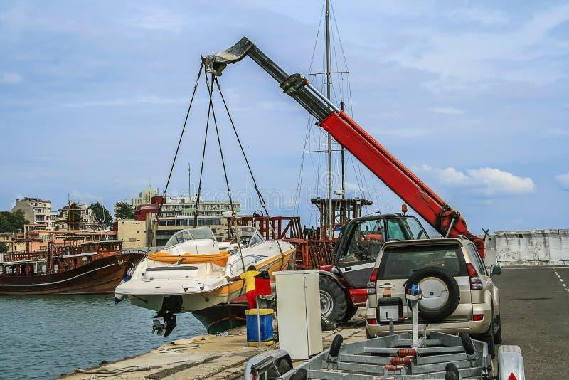 La grue soulève un bateau photographie stock libre de droits