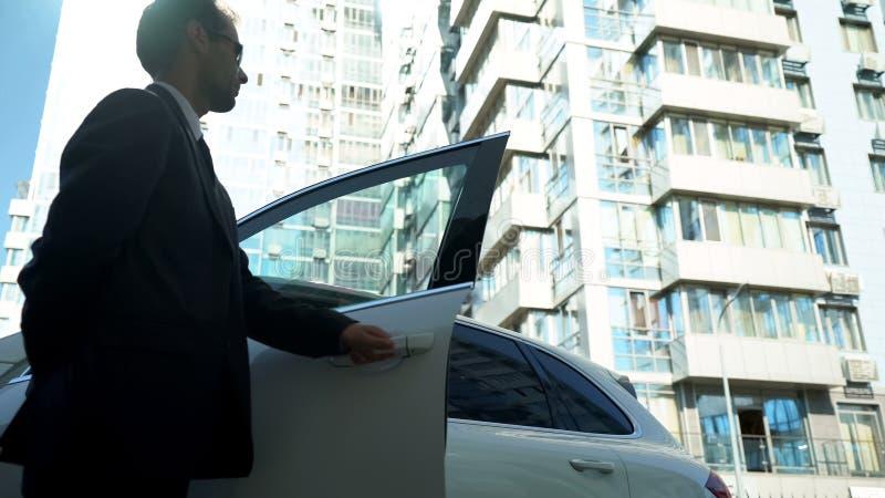La guardia giurata apre le porte di automobile al capo di signora, la sicurezza per il politico, vista dal basso immagine stock libera da diritti