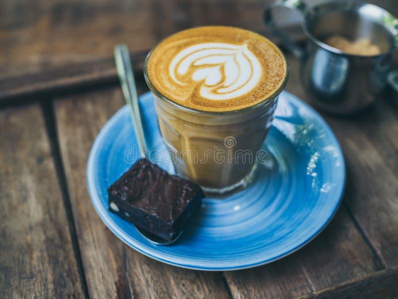 La guarnizione piccola del caffè del Latte con l'arte del fiore da latte in piccolo vetro con un pezzo di brownie casalinghi aggl fotografie stock libere da diritti