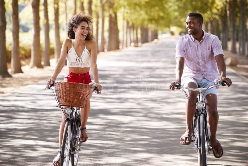 La guida giovane di risata delle coppie va in bicicletta su una strada soleggiata immagini stock