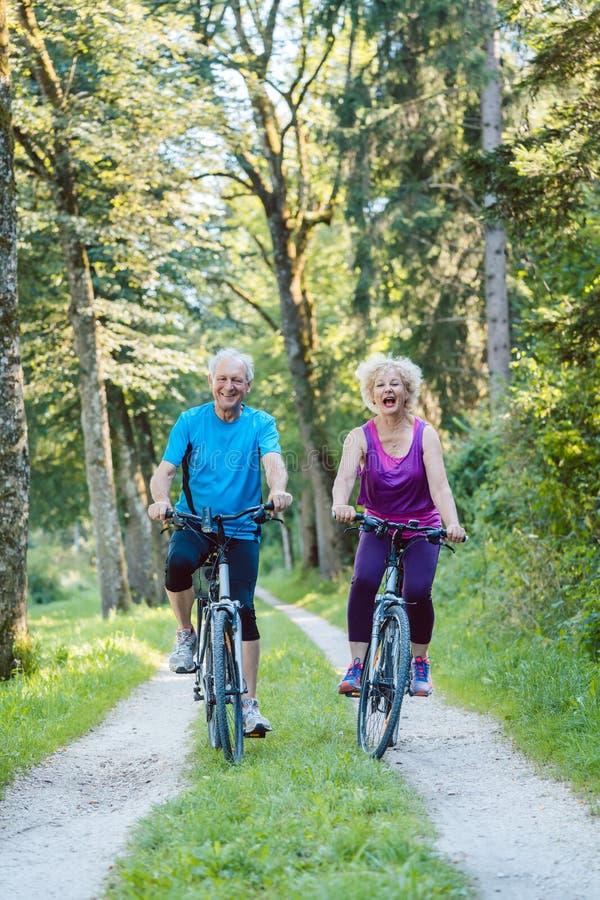 La guida senior felice e attiva delle coppie va in bicicletta all'aperto nella p immagini stock