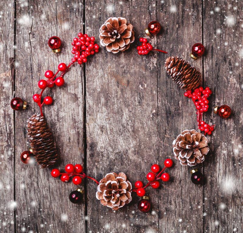 La guirlande de Noël du sapin s'embranche, les cônes, décorations rouges sur le fond en bois foncé image stock