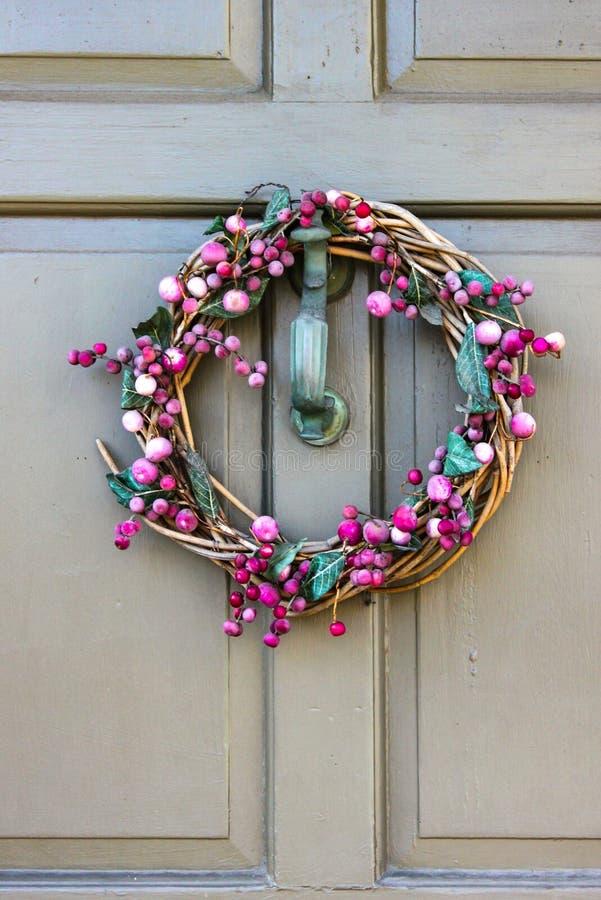 La guirlande pourpre assez simple avec des vignes et des feuilles et fruit accroche sur un heurtoir de porte d'une porte peinte photos stock