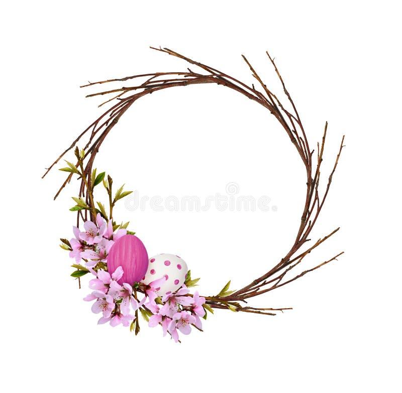 La guirlande ronde des brindilles sèches avec des branches de ressort des fleurs et des feuilles de pêche et la Pâques ont peint  image stock