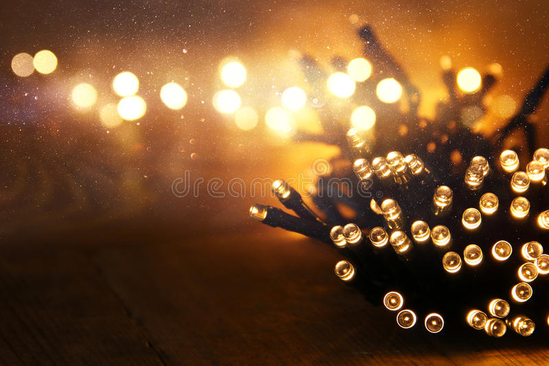 La guirnalda caliente del oro de la Navidad se enciende en fondo rústico de madera Imagen filtrada foto de archivo