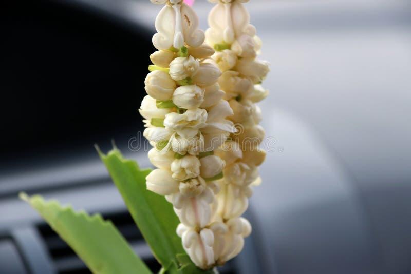 La guirnalda de la flor contiene de la flor de la corona y de la ejecución del jazmín en el coche fotografía de archivo