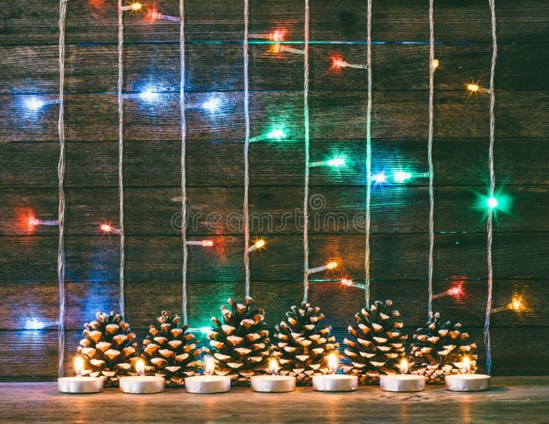 La guirnalda de las luces, los conos de abeto y las velas multicolores en el fondo del granero viejo sube fotografía de archivo